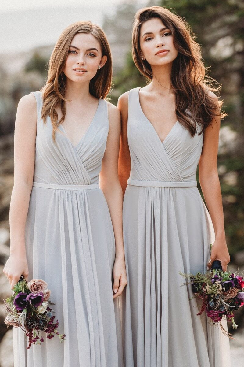 Bridesmaids wearing long light gray dresses